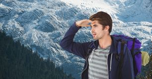 Male hiker shielding eyes while carrying backpack on mountain Stock Photos