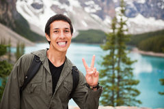 Male hiker showing you the 'V' sign. Happy male hiker showing you the victory sign against natural background royalty free stock photos