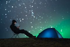 A male hiker sits on a chair at night and uses a smartphone. Tent with lighting and star bokeh in the background. Slight aurora royalty free stock images