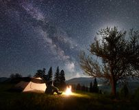 Male hiker enjoyng night camping near tourist tent at campfire under blue starry sky and Milky way royalty free stock photography