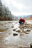 Male hiker sitting stone in river Royalty Free Stock Images
