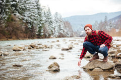 Male hiker sitting on the stone and testing wate. R in the river Stock Images