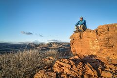 Male hiker sitting on a top of sandstone rock formation. Senior male hiker is sitting on a top of sandstone rock formation and watching sunset over Red Mountain Royalty Free Stock Photo