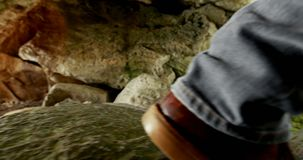 Male hiker standing with backpack near a cave 4k stock video