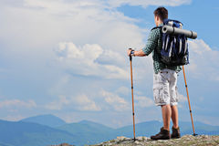 Male hiker standing on a mountain top. And holding hiking poles Royalty Free Stock Photography
