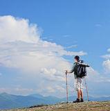 Male hiker standing on a mountain top. And holding hiking poles shot with tilt and shift lens Royalty Free Stock Photos