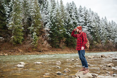 Male hiker standing on the stone in river. And looking into the distance Royalty Free Stock Photo