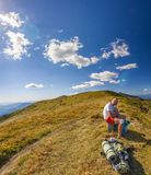 Male hiker standing on top of the rocky peak overlooking mountain landscape. Stock Image