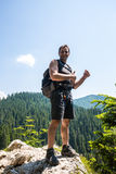 Male hiker standing on a very high cliff Stock Photo