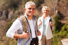 Male hiker standing wife. Handsome senior male hiker standing in front wife royalty free stock photography