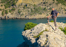 Male hiker on a stony sea shore Royalty Free Stock Photos