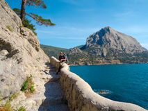 Male hiker on a stony sea shore Stock Photos