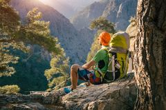 Male hiker taking a moment to watch sunset. Male traveler sitting on a rock high in the mountains lit with sunshine and regaining his strength.Tahtali, Turkey Royalty Free Stock Photography
