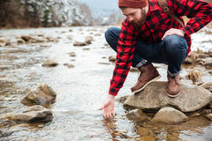 Male hiker testing water. In the river Stock Photos