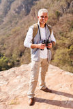 Male hiker top mountain. Handsome senior male hiker standing on top of mountain royalty free stock photos