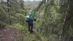 Male hiker with travel rucksack standing on the edge of high mountain during summer trek. Stock footage. Male explower
