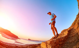 Male hiker, traveler runs on the trailagainst sea and blue sky. Male hiker, traveler runs on the trail against sea and blue sky at the sunset. Balos beach on Stock Photo