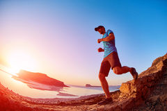 Male hiker, traveler runs on the trailagainst sea and blue sky. Male hiker, traveler runs on the trail against sea and blue sky at the sunset. Balos beach on Stock Image