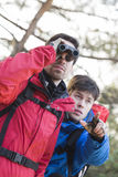 Male hiker using binoculars while friend showing him something in forest Royalty Free Stock Images