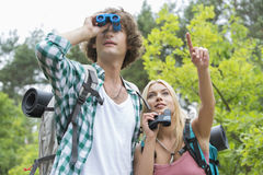 Male hiker using binoculars while girlfriend showing something in forest Stock Photo
