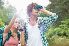 Male hiker using binoculars while woman showing him something in forest Royalty Free Stock Image