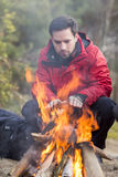 Male hiker warming his hands at campfire in forest Royalty Free Stock Photos