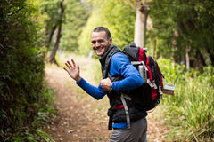 Male hiker waving hand while walking in forest. Portrait of male hiker waving hand while walking in forest Royalty Free Stock Photo