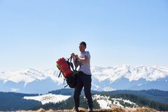 Male hiker with backpack in the mountains. Male hiker wearing his backpack preparing for a hike in the mountains copyspace preparation sporty lifestyle activity Royalty Free Stock Photos