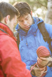 Male hikers looking at rope in forest Stock Image