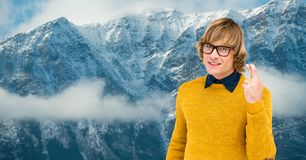 Male hipster with crossed fingers against snow covered mountains. Digital composite of Male hipster with crossed fingers against snow covered mountains Royalty Free Stock Photo