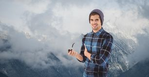 Male hipster holding smoking pipe against fog covering mountains Royalty Free Stock Images