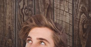 Male hipster looking away against wooden wall Royalty Free Stock Images