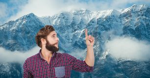 Male hipster pointing against snow covered mountains Royalty Free Stock Photos