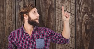 Male hipster pointing upwards against wooden wall Royalty Free Stock Photography