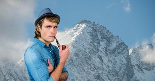 Male hipster smoking pipe against snow covered mountains Royalty Free Stock Images