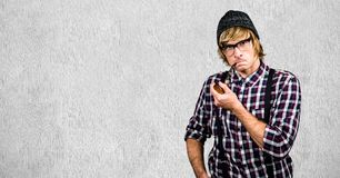 Male hipster smoking pipe against wall Stock Images