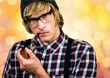 Male hipster smoking pipe over bokeh Royalty Free Stock Photos