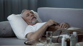 Male in his 60s sleeping in bed at home, pills and fluids standing on the table. Stock footage Stock Images