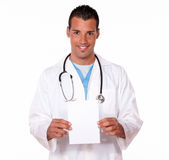Male hispanic doctor holding a blank card Royalty Free Stock Image