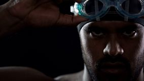 Male Hispanic swimmer wearing goggles, athlete seriously looking at camera royalty free stock images