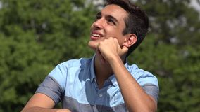 Male Hispanic Teenager Daydreaming. A handsome hispanic male teen stock footage