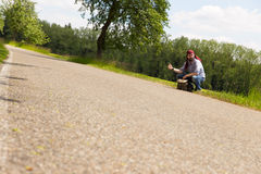 Male hitchhiker is sitting on a street Royalty Free Stock Image