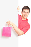 Male holding a bag and standing behind panel Stock Images