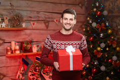 Male holding a big red ribbon gift box and smiling. Stock Photos
