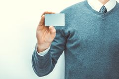 Male holding blank card of grey color in his right hand. Male holding blank card of grey color in one hand Royalty Free Stock Photos