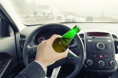 Male holding bottle of beer while driving car Stock Images