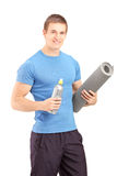 Male holding a bottle of refreshment drink and a mat after an ex. A male holding a bottle of refreshment drink and a mat after an excerise isolated on white Stock Image