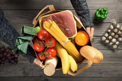 Male holding brown paper bag full of different healthy food. On wooden table, top view Stock Photo
