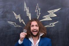 Male holding bulb, idea bulb concept. Shaggy charismatic man with beard have some groundbraking idea Stock Photography