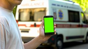 Male holding cell phone, ambulance on background, application for emergency call stock images